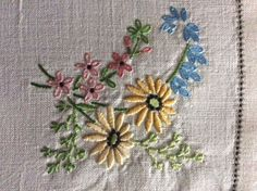 "A beautiful vintage linen hand embroidered tray cloth or table centre piece. Crisp, smooth, quality linen cloth with a double edge and a hand sewn ladderwork detail. Lovely hand embroidery on this cloth ~ neat, raised, compact work using gorgeous coloured threads to form wonderful floral displays in each corner, with a larger display in one corner, which includes anemones. So pretty. In superb, freshly laundered, crisp, starched condition and measures 18"" x 12 1/2"" 