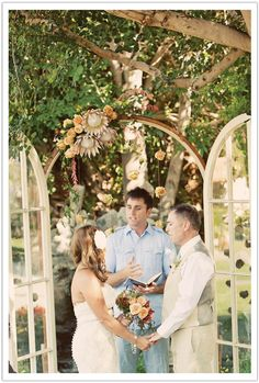 The couple wed under a vintage door frame with king proteas and floating peach roses in front of La Quinta's garden waterfall.  Flowers by Arrangements, Event Design by Alchemy Fine Events