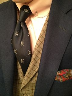 Gatsby style..Dark grey suit, black tie with checkered vest and paisley pocket square.