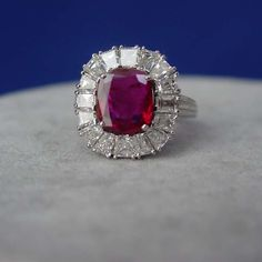 A ruby and diamond ring mounted in platinum, centering a cushion cut ruby weighing 2.67 carats. The ruby is surrounded by diamonds weighing approximately 3.50 carats in total.