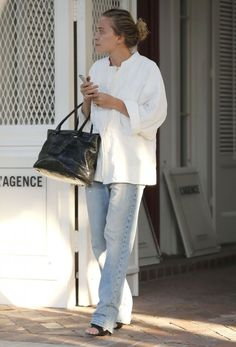 Mary-Kate Olsen goes for light wash jeans and a loose fit button down. #LA