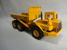"""This Die Cast Caterpillar Model D350D Articulated Dump Truck was issued in 1992 by ERTL of Dyersville, Iowa. It is made of highly detailed quality die cast metal, has articulated/oscillated steering, rubber tires and a movable hydraulic dump box. It is in 1/50th scale and is 7 1/2"""" long x 3 1/2"""" tall."""