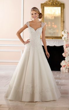 This keyhole back princess wedding dress from Stella York is a traditional bride's dream gown! Lace and tulle over Royal organza in a modified A-line silhouette creates a magical moment when twinkling beading is added, giving an extra pop of glamour. A lace detail surrounds the skirt just above the hem, mirroring the lace edges of the sparkling bodice. Wide straps come across the back, forming an elegant keyhole back. This stunning princess ball gown is also available in plus sizes.