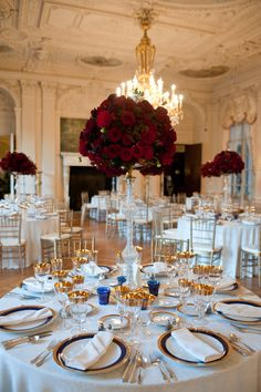 Gorgeous gold and blue rimmed chargers, accented with gold stemware and deep red roses made this Rosecliff Mansion room sparkle.