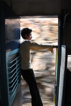 Holding on tight - riding trains in India. Photo by Justina Lee