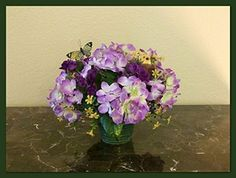 Silk Floral Arrangement with Purple Hydrangeas, Birds and Butterflies. Pretty centerpiece with purple hydrangeas, purple spray roses, 2 cute birds and a butterfly in a green ceramic vase. Looks pretty from every angle. Would look wonderful on a dining table or coffee table. Measures 10 inches tall x 13 inches wide.