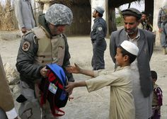 Gary Sinise (left) hands a back pack to an Afghan child Nov. 23, 2009. Mr. Sinise stopped at the school, on his way to Forward Operating Base Goshta, to hand out back packs full of school supplies, shoes and other necessities to local children