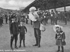 A corporal in the Royal Army Medical Corps poses with his children at Aldershot Railway Station prior to his departure on active service.  This is one of a series of postcards taken in 1914 when it was believed that the war would be soon over.  HMCMS:DPABBM57