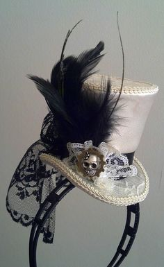 Mini top hat striking in ivory and black. Metal sugar skull and Gear side piece. Handmade upon your order. Our design is on a black, white or brown head band or small metal hair clip for easy wear, please specify when ordering. Satin, lace and other fine fabrics used. All hand made, and our design. Discount on multiple hats. Note, this style of hat can be custom colors occasions you need it to match an outfit. Please inquire, we love custom orders.   Hat design elements may vary slightly…