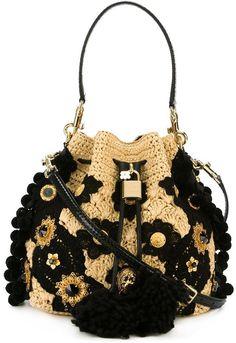 Dolce & Gabbana 'Claudia' bucket shoulder bag. Natural and black raffia with an adjustable shoulder strap, a drawstring fastening, a padlock fastening detail and gold-tone hardware. $6,695 #handbags #designerhandbags #purse #clutch #designerbags