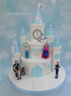 A 3 tier Frozen themed princess castle cake with matching vanilla sugar cookies used for party favours. The models were plastic supplied by the client for her to daughter to play with once the cake had gone!