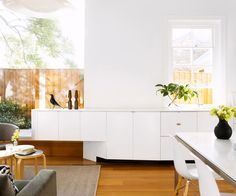 """Creating a visual connection, the kitchen area extends into the living space with streamlined joinery.   **Joinery** in two-pack polyurethane in [Dulux](http://www.dulux.com.au/