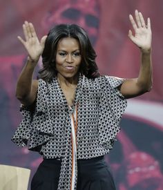 First lady Michelle Obama waves before speaking at The University of Akron in a black and white blouse.