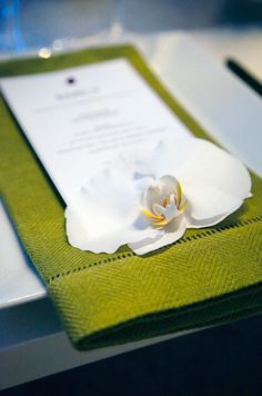 A white phalaenopsis orchid tops a personalized dinner menu and lime green hemstitched napkin.