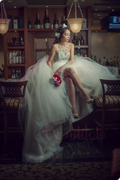 A beautiful bride sitting on the bar at Chateau Vaudreuil