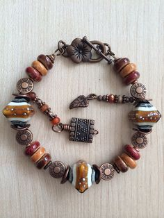 Beautiful Lampwork bead bracelet with ceramic beads in shades of brown , and copper accent beads with 2 dangles for highlights.