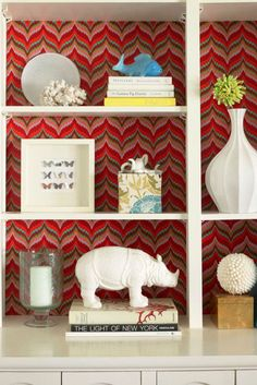 Give your bookshelf a fashion moment. A patterned backdrop is gorgeous–and so easy. Just measure the space of each cubby and cut a piece of cardboard to those dimensions. (Check the fit before going further.) Using fabric, wallpaper, or even your favorite wrapping paper, tightly wrap the cardboard like a gift. Push it to the back of the shelf: done!   - Redbook.com