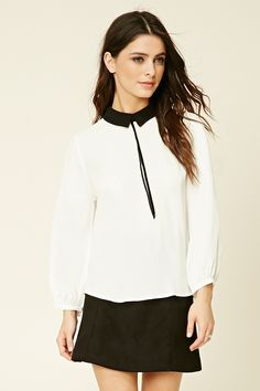 A woven top with a contrast basic collar, a velvet self-tie accent at the neckline, a buttoned keyhole back, and button-cuff long sleeves.