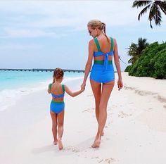 madre e hija tomadas de las manos caminando por la playa