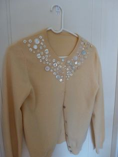 Cardigan embellished with buttons. Scroll down on page for the post at The Spiritual Knitter