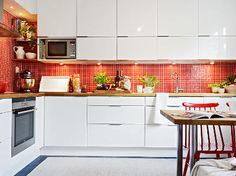 Swedish kitchen with red backsplash in glass mosaic tile - stadshem.se via atticmag