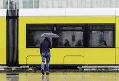 https://flic.kr/p/v4WVFE   Man, Umbrella, Tram   Man with Umbrella in front of Tram