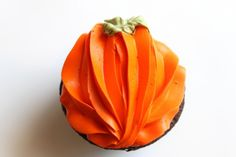 To pipe a pumpkin apply three lines of frosting one on each outer edge from top to bottom and one down the middle, then apply two additional lines in between the first three lines and add some green frosting with a leaf tip.