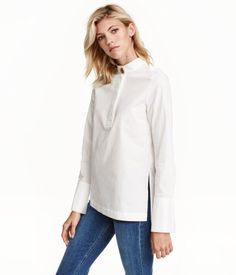 White. Straight-cut shirt in airy, woven cotton fabric. Small stand-up collar with large metal button at front, concealed button placket, wide cuffs with