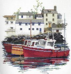 An attractive landscape picture with a row of fishing boats in harbour and whitewashed waterside cottages.