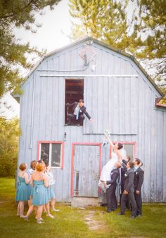 Maybe have the bride on a ladder & have the groomsmen on one side & the bridesmaids on the other supporting the ladder as the bride & groom reach for each other.