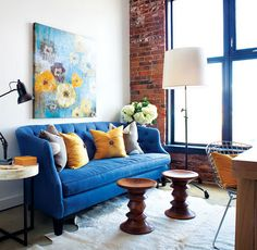 love the huge window with the brick wall, and how the bright blue of the sofa works with it