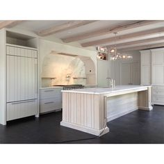 a beautiful white kitchen with white washed wood beams and a white washed wood island. Notice the combination of vertical groove and paneled doors in this kitchen Kitchen Hoods, Cozy Kitchen, Kitchen On A Budget, Kitchen Backsplash, Transitional Living Rooms, Transitional Kitchen, Transitional Decor, Kitchen Interior, Kitchen Design