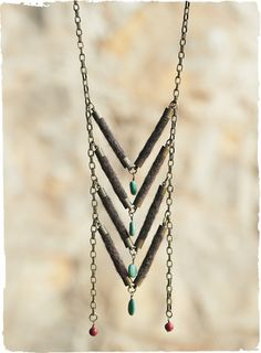 Hand-felted wool chevrons, dotted with turquoise, fall from a brass chain necklace.