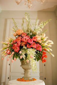 Urn with tulips, roses, peonies, calla lilies, orchids, & stock(?), surrounded by kumquats.