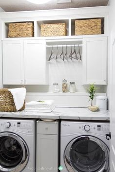 White laundry room features a white front load washer and dryer tucked under a calacatta marble like formica countertop, Lowes Formica Brand Laminate Calacatta Marble, placed under a built-in shelf ledge and cabinets with overhead cubbies.