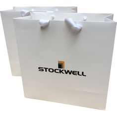 Branded event bag. Printed gift bag for events. Goodie bag with corporate logo branded / embossed. White matte paper bag with white grosgrain ribbon handles.