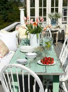 Weathered turquoise painted table. White chairs and pillows. Tulip bucket centerpiece.