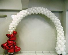 White balloon arch with red hearts