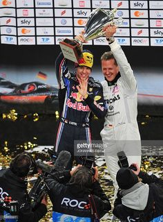 German Formula One World Champion Sebastian Vettel (R) and German F1 driver and seven times World champion Michael Schumacher celebrate with the tropht after winning the Nations Cup of the Race of Champions (ROC) in Duesseldorf, western Germany, on November 27, 2010. The race, featuring 28 motor racing World Champions takes place on the weekend of 27 and 28 November and the drivers will compete following the knockout system on a 1000 meter race track at Esprit Arena.