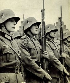 Wehrmacht soldiers on parade. You can tell this photo is per-war from the helmets, notice the extended brim.