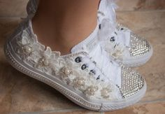 Here we present our latest offering from our luxury wedding shoe range. We believe every bride should feel special on her wedding day and these shoes reflect that. We only use genuine swarovski crystals on our luxury wedding shoes as they sparkle like no other crystals.  These converse wedding trainers are real authentic Converse not a cheap copy. We have decorated the Converse with hundreds of swarovski crystals and delicate cream lace flowers with pearls,accents. The laces are organza…