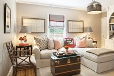 Neutral TV room with BM Ashley Gray Walls, pops of Orange with the Hermes throw, schumacher betwixt pillows. Louis Vuitton trunk for coffee table . Lee Industries sectional