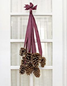 Was just given several dozen giant sequoia pine cones, the size of bowling balls - this would be interesting!  easy and elegant  8 six-inch pine cones and 8 two-foot-long pieces of silk ribbon. Use a glue gun and glue a cone to each ribbon.Then collect all the ribbon ends and stagger them so that the cones fall nicely.Tie together and hang on your door.