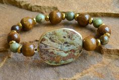 """ Green opal, wood and gold hematite beads with a gold trimmed, green opal focal. Bracelet will fit 6.5"""" - 7"""" wrist. Stones may vary slightly. Customization available upon request. Perfect for stackin"""