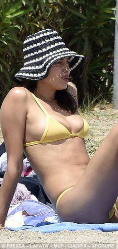 Hat's a good look! The bikini-clad beauty donned a floppy black and white striped hat on the outing