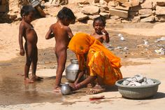 Children getting a bath from their mother in the street, Jaisalmer, India. Photo by Jolly Sienda Photography.