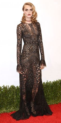 Cara Delevingne mastered Goth glam when she arrived on the red carpet in a see-through black lace Elie Saab gown with a flouncy hem and bell sleeves. Tiny gold hoops, a gold choker, and strappy Stuart Weitzman sandals completed her look.