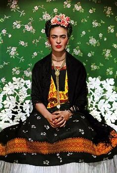 Frida Kahlo portrait. Love this portrait of Frida Kahlo because it feels like so many of her self portraits that she did, with the same hair style, flowers in her hair, and green and floral background. She looks like a painting here to me.