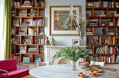 Eclectic and mod living room with floor-to-ceiling bookshelves.