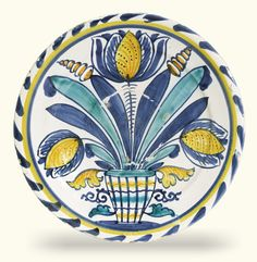 A Brislington delftware blue-dash tulip charger, circa 1685-1700, painted in blue, yellow, ochre and turquoise with three tulips and buds standing in a striped vase flanked by scrolling leaves 35cm., 13 3/4 in.diameter